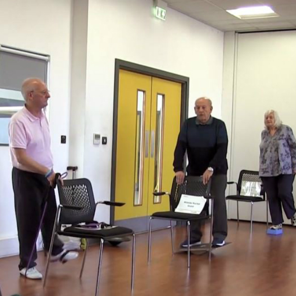 Three people taking part in an ESCAPE-Pain Class and completing leg exercises and stretches