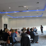 An event with a room full of guests listening to a speaker present