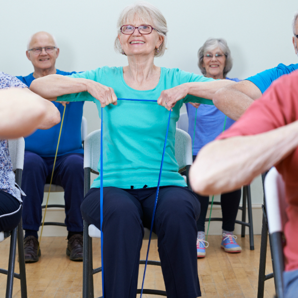 Elderly woman taking part in chair-based exercise class