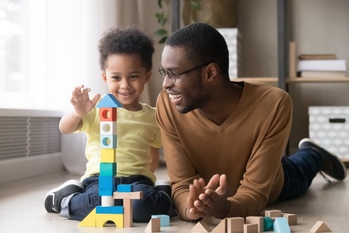 Young child and father learning and playing with blocks on the floor