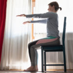 Woman at home doing exercise sat on a chair