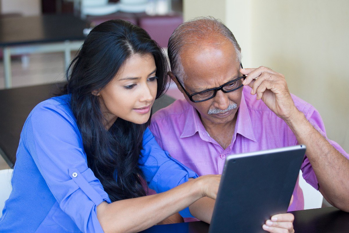 Young woman and elderly man using tablet computer
