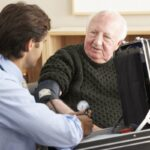Elderly man has blood pressure checked by doctor