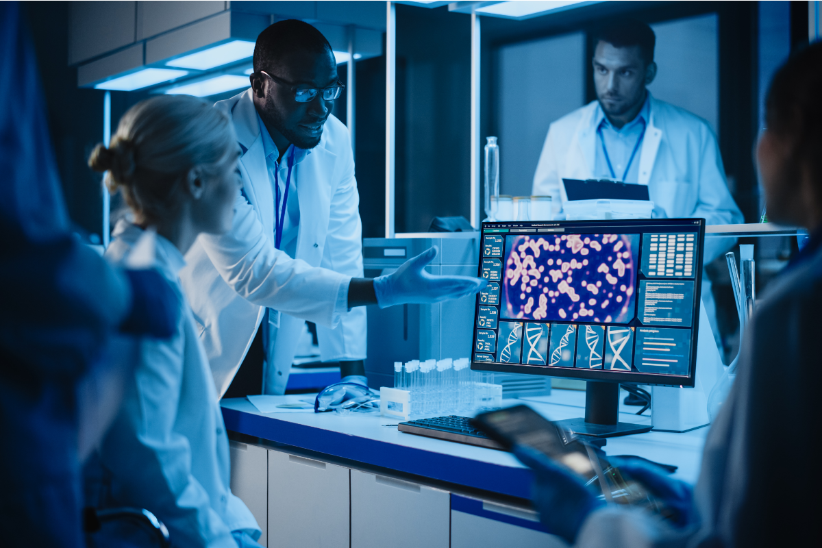 Multiple Health researchers looking and clinical research on a computer screen