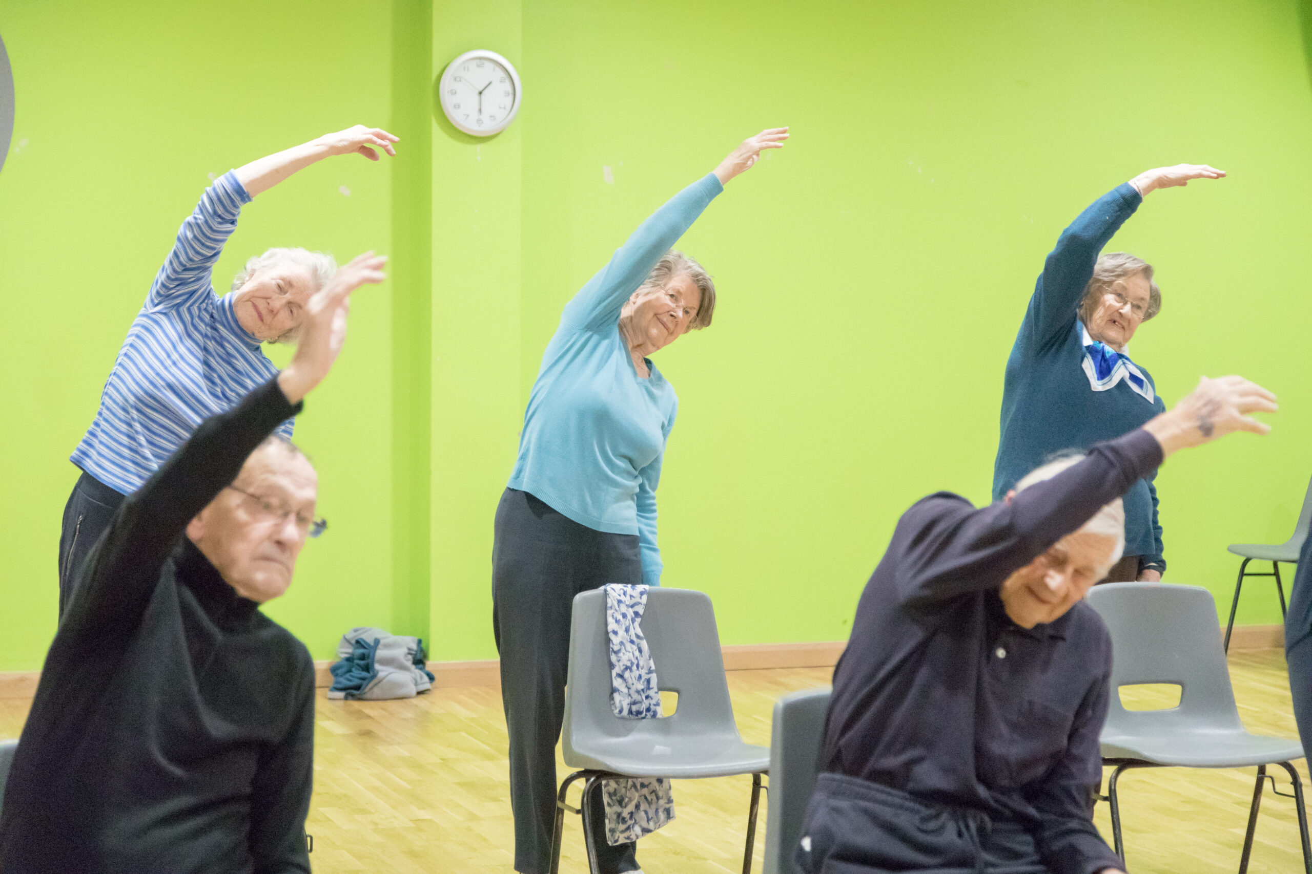 Elderly people exercising in a group.