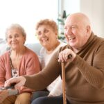 Two older women and an older man enjoying watching digital television together